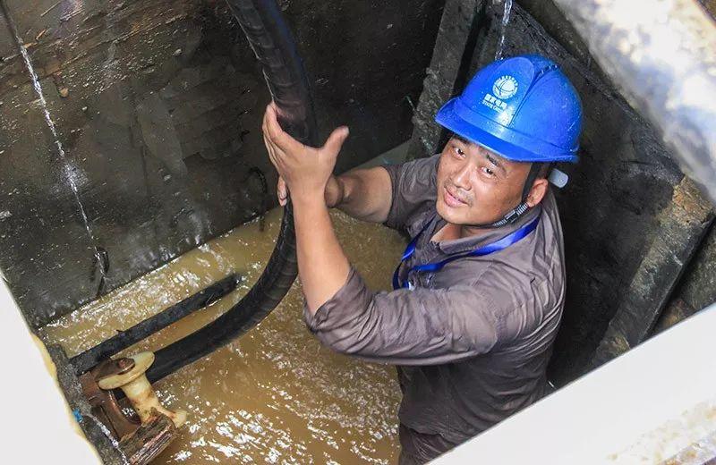 ▲7月26日,湖北武汉江夏区供电公司员工黄威在江夏区花山郡小区竖井里敷设电缆。