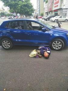 老人躺在蓝色轿车旁。