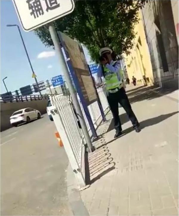 一名交警手持设备站在马路旁的牌子后