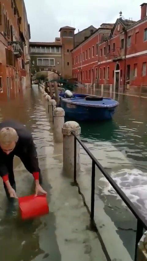 辛勤的水城威尼斯人民正在将道路上的水耐心地一桶一桶地倒进河里