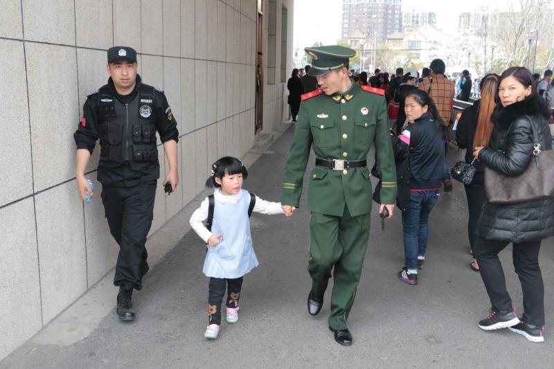 武警战士张志浩为迷路女孩找父母。何舒俊 摄