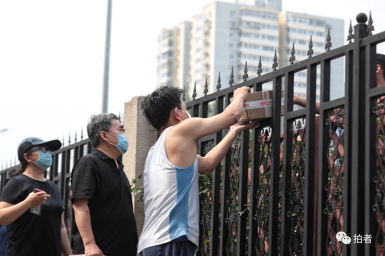 △6月20日,居民隔著小區欄桿領取快遞。小區封閉后,快遞員不能進入小區,小區圍欄成為快遞的交接點。