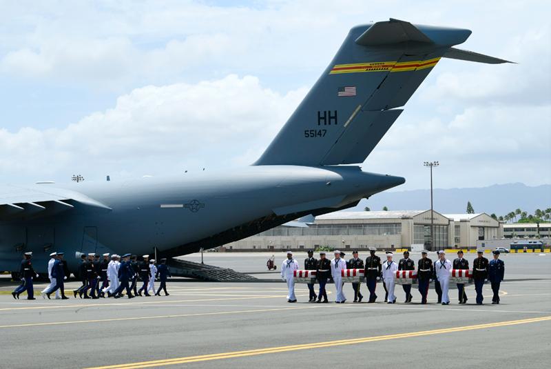 美军士兵从运输机上,将棺材抬下。(韩联社)