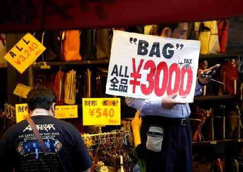 5月16日,在日本东京,一家商店的店员(右)举着标有商品价格的牌子吸引消费者。(新华/路透)