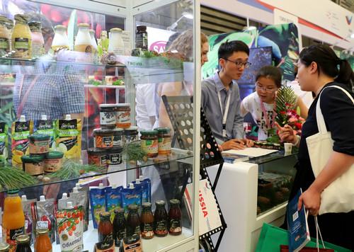 5月16日,第十九届中国国际食品和饮料展览会在上海开幕。这是参展商向观众介绍俄罗斯出产的食品。新华社记者 刘颖 摄