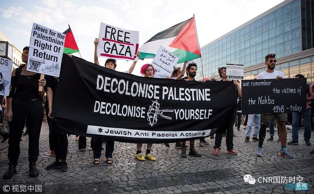 当地时间2018年5月14日,德国柏林,民众挥舞巴勒斯坦国旗,抗议美国将驻以色列大使馆搬迁至耶路撒冷。