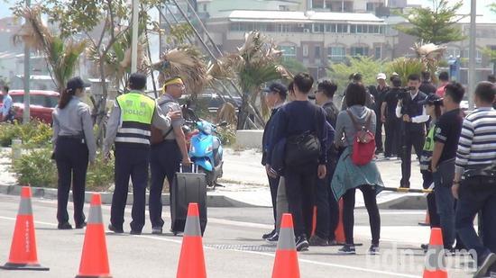 台湾退警协会执行长陈志杰拿着大声公(扩音器)被警力劝离。(图片来源:台湾《联合报》)