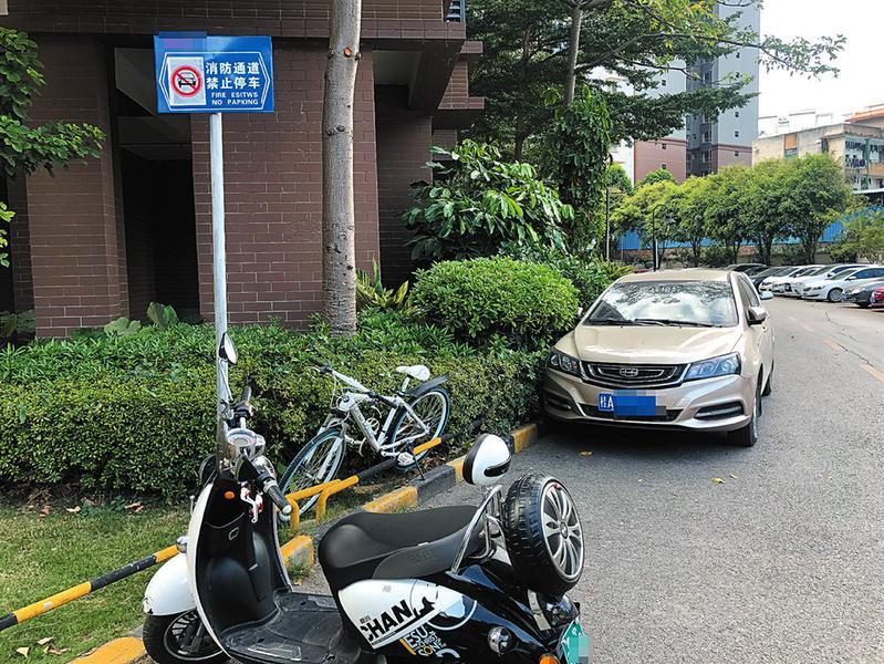 明秀路某小区消防通道上有禁止停车的警示牌,仍有电动自行车和小车停在这里记者宋延康摄