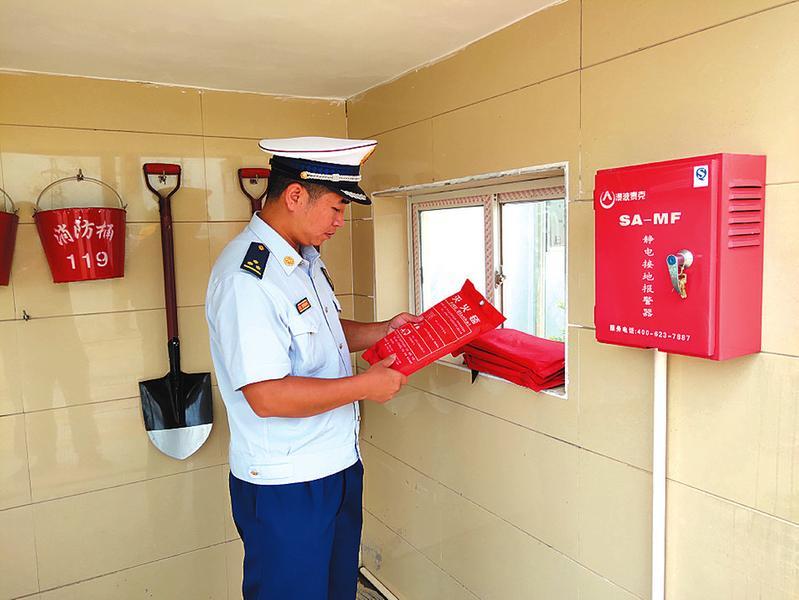 消防人员仔细检查消防设施  通讯员江杰摄