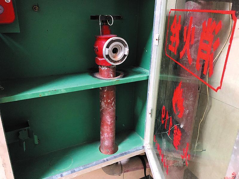 某小区电梯边上的消火栓(箱)内没有灭火水带 记者宋延康摄