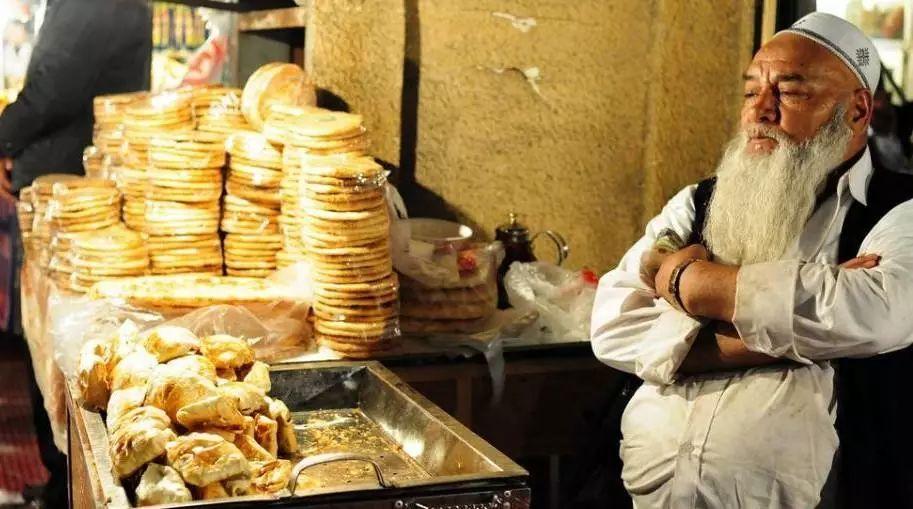 一位老人在出售烤包子、烤馕饼。 来源:中新网