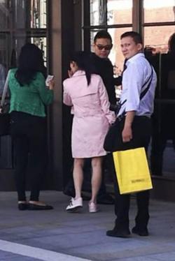 英拉(左一)身穿绿色外套,一名身穿白色衬衫的男子(右一)紧随英拉身后,手中拿着一个购物袋。(图源:《曼谷邮报》)