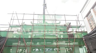 吊车正将牌坊上的构件一件件拆卸下来。
