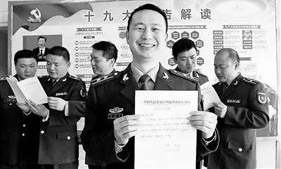 △现役转改文职人员熊成臣(右三)展示转改申请书。