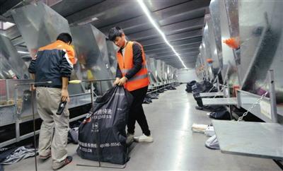 去年11月8日晚,申通郑州分拣中心,工作人员把快件扫描装包。图/视觉中国