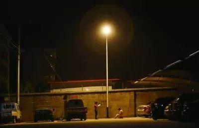 为了不影响邻居休息,凌晨两点,爸爸陪孩子在路灯下读书(图源:中国新闻网)