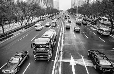 昨天,在东三环国贸桥附近,北京环卫集团城市机扫公司一辆纯电动洒水车进行冲刷作业,以降低道路尘土残存量。 本报记者 武亦彬摄