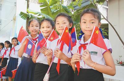 在诵读会现场,琅勃拉邦新华学校小学生手持中老两国国旗.