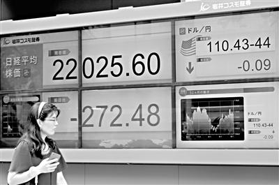 8月13日,在日本東京,行人經過一處股市信息顯示屏。