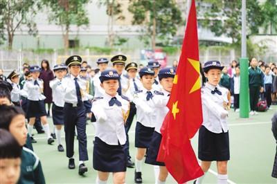 香港爱国学校的小学生在校园升旗礼上(图源:人民日报海外版)