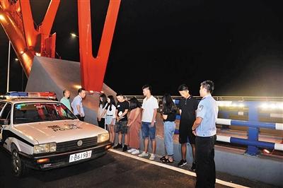 民警三次爬上大桥主拱圈,将7名大学生成功救下。