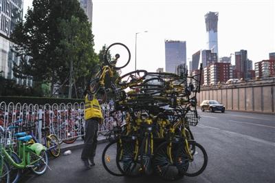 2017年9月15日,大望桥附近,此处共享单车过剩,一位工作人员正在转运多余的单车。资料图片/新京报记者 彭子洋 摄