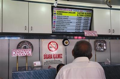 当地时间8月10日,土耳其安卡拉,一名男子看着显示汇率的屏幕,当日土耳其里拉对国际主要货币汇率大幅下跌。里拉对美元汇率一周内跌幅已超13%。 新华社发