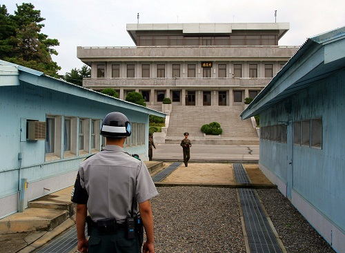 资料图:这是2007年10月4日在朝鲜半岛中部的板门店拍摄的一名韩国宪兵(前)和朝鲜人民军军官分别在军事分界线两侧执勤的资料照片。 新华社记者 龚兵 摄