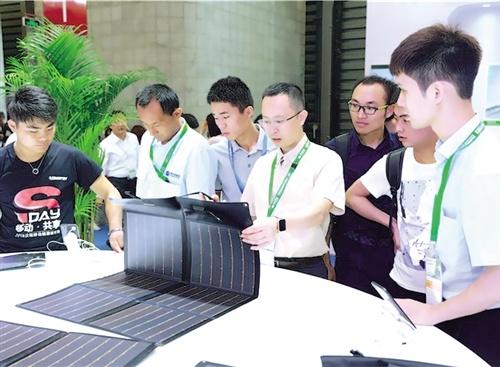 消费者在体验汉能生产的薄膜太阳能发电纸。 本报记者 王轶辰摄