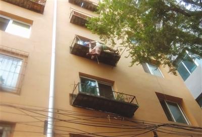 4楼花台上,民警李晓东紧紧地抓住跳楼男子。警方供图