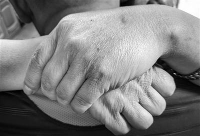 抱着分离几十年的亲生儿子,谭女士的双手不停地颤抖。