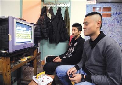 """2019-09-18,天津""""80年代""""主题餐厅内,两名顾客在玩小霸王游戏机。B04-B05版图/视觉中国"""