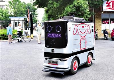 正在进行订单配送的京东配送机器人吸引了路人的目光。资料图片