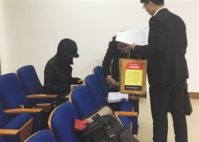 严密包裹着面部的原告王女士(左一)坐在法庭旁听席上参与庭审。新京报记者 左燕燕 摄
