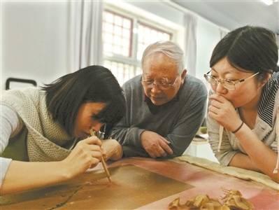 徐建华老师指导张笑艳展开修复工作。
