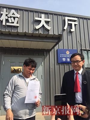 宣判后,刘忠林在律师与姐夫的陪同下走出法庭,向媒体出示无罪判决书。新京报记者王巍 摄