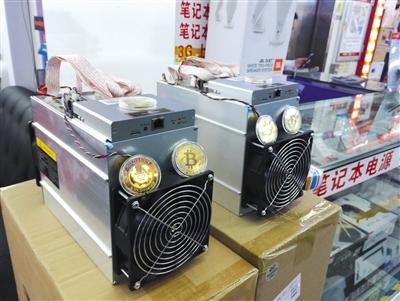 5月4日,深圳华强北赛格电子市场一家档口展示的数字货币矿机和比特币模型。