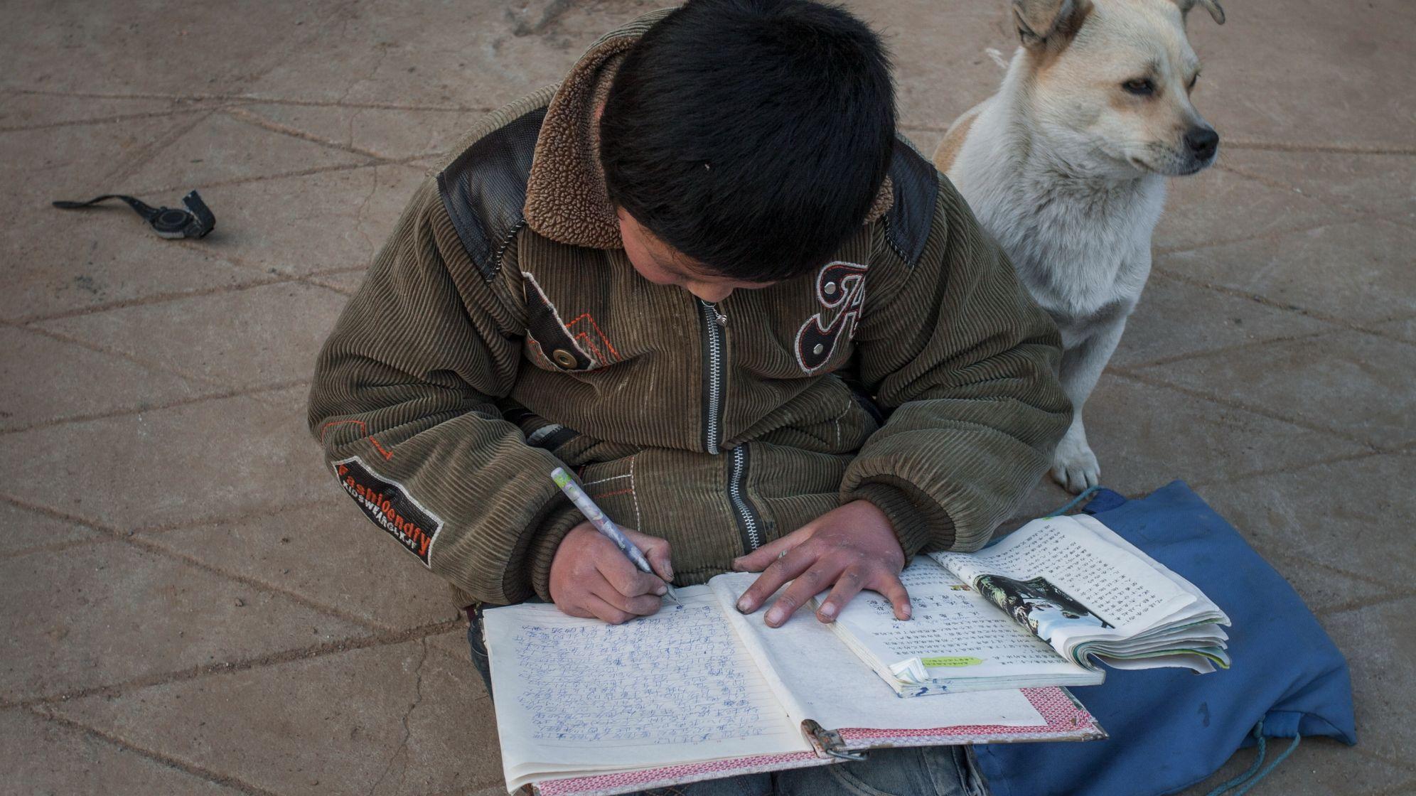 2009年2月,小学生刘春莹在玩伴的家门口写作业。受访者供图