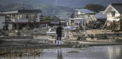 日本灾民站在因千曲川溃堤而遭受洪灾的住宅区前( 《每日新闻》 )