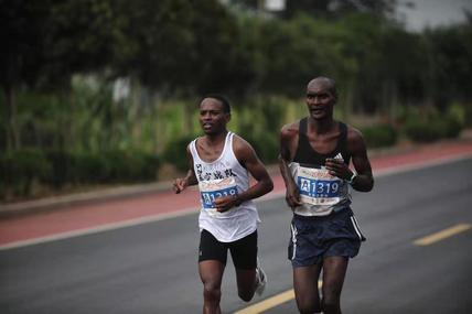 枣庄马拉松32公里处,两名非洲选手率先通过,领跑员赤脚跑过