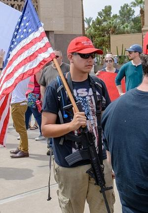 一名男子在抗议控枪游行活动中斜跨着AR-15自动步枪。(图源:《每日邮报》)