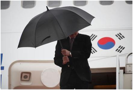 强风袭去,李洛渊单脚松握雨伞 图源:《百姓日报》