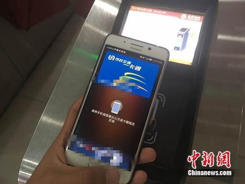 资料图:乘客用手机刷公交卡 中新网记者 张尼 摄