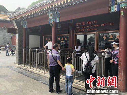 5月10日,北京北海公园门口,一名小女孩正在排队购票。 冷昊阳 摄