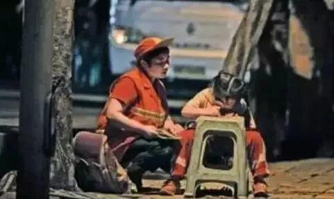 环卫工妈妈在路边陪孩子写作业(图源:网络)