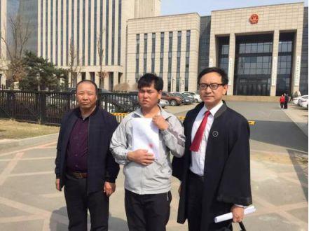 宣判后,刘忠林(中)在张宇鹏律师(右)与姐夫的陪同下走出法庭,向媒体出示无罪判决书。(来源:新京报)