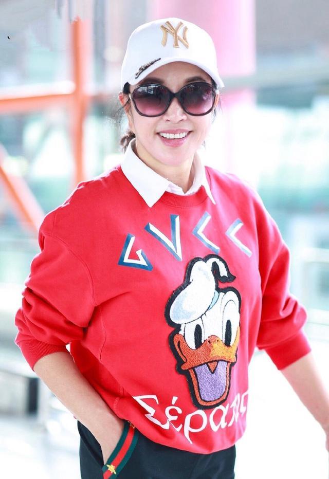 刘晓庆真抗老,穿大红色卫衣搭配运动裤走机场,唐老鸭印花真吸睛