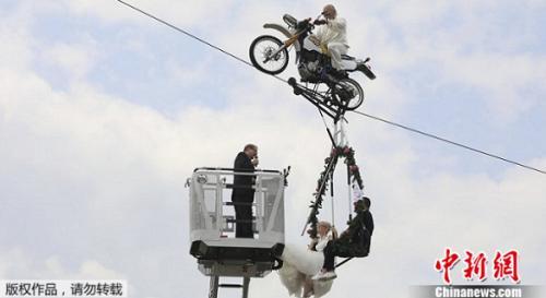 """德国东部一对新人选择骑着用钢索吊起的摩托车,举办一场""""空中的婚礼""""。"""