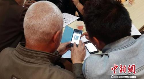 资料图:老年人正在向年轻人请教如何使用微信。佘丽莎 摄
