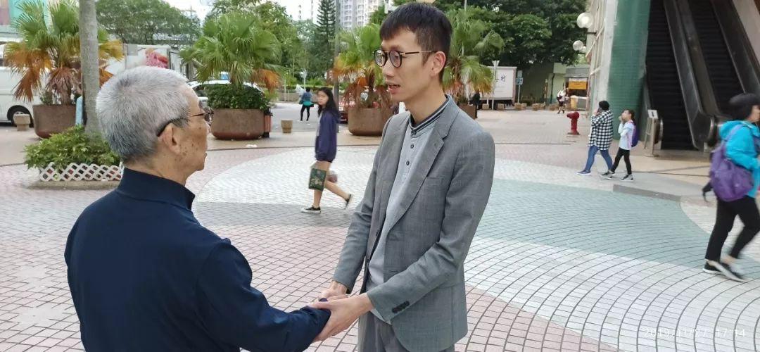 陈志豪(右)与一位老人握手。
